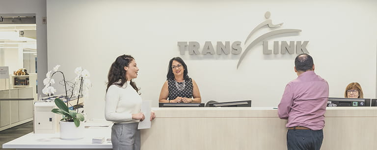 Two people standing in front of a reception desk inside TransLink's head office