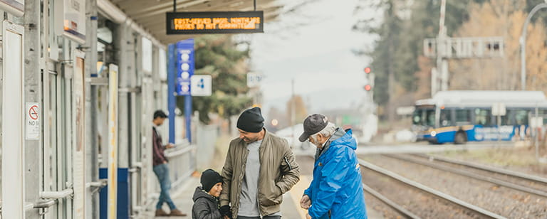 A family waiting for a West Coast Express train to arrive at the station platform