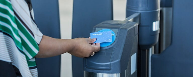 A person tapping their Compass card to open the fare gate