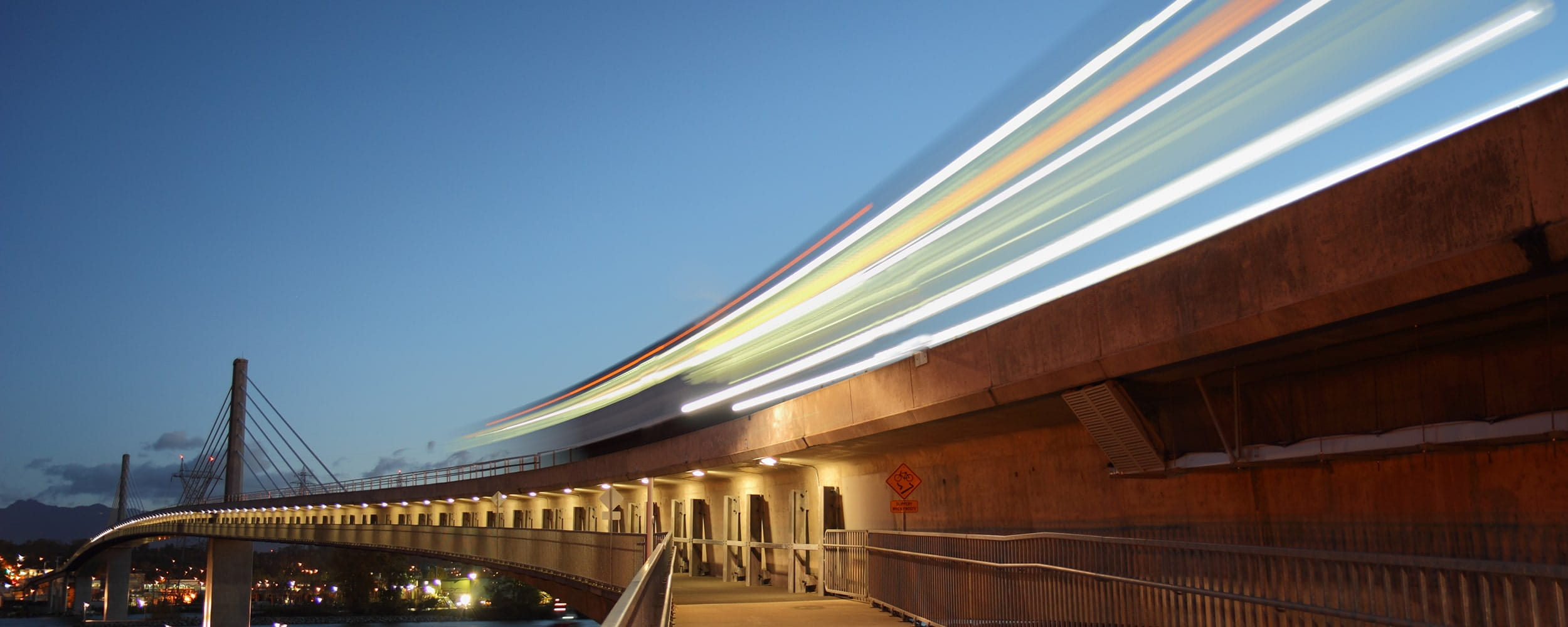 A SkyTrain running on rail against a clear evening sky