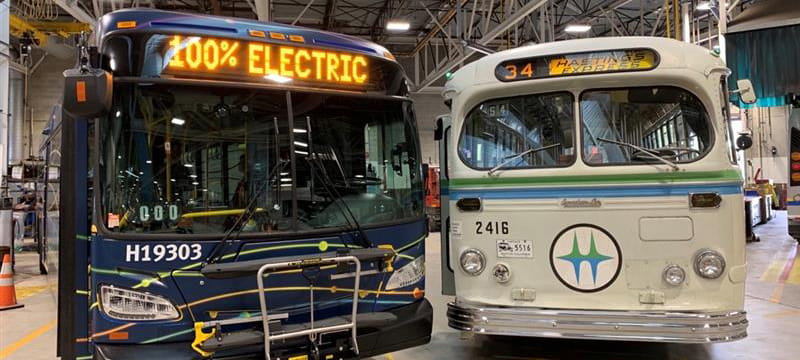 An electric bus parked next to a retro TransLink bus