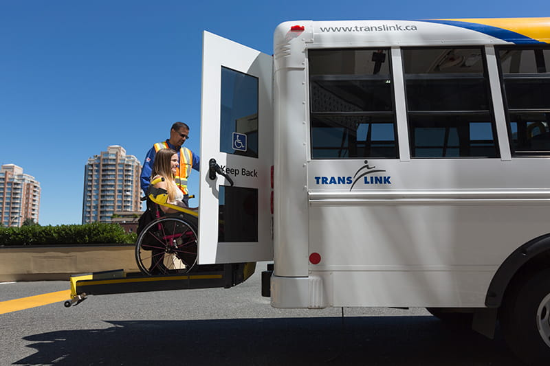 A HandyDART Operator assisting a woman in a wheelchair to board a HandyDART shuttle